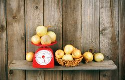 Onions on scales and in a basket Royalty Free Stock Photos