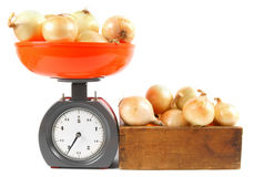 Onions on scales and in a box Stock Photo