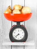 Onions on scales Royalty Free Stock Photo