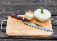 Onions, squash and knife on board Royalty Free Stock Image