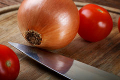 Onions tomatoes and a knife Royalty Free Stock Images