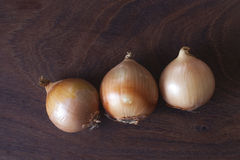 Onions. 3 onions on a wooden background Stock Images