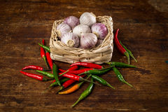 Onions on a wooden basket. Dried red hot chilli on a wooden basket. Onions and garlic Royalty Free Stock Photos