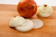Onions on wooden table Stock Images