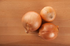 Onions on wooden table Royalty Free Stock Images