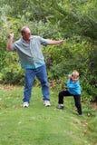 Onkel unterrichtet Jungen, Steine zu überspringen Lizenzfreie Stockfotos