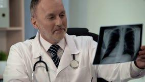 Onkologe, der Röntgenstrahl sieht und an der wunderbaren Wiederaufnahme der Patienten von Krebs sich freut stockfoto