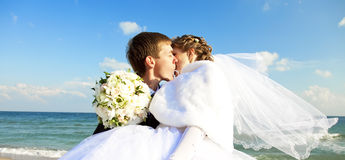 Onlangs echtpaar het kussen op het strand. Stock Afbeelding