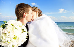 Onlangs echtpaar het kussen op het strand. Stock Afbeeldingen