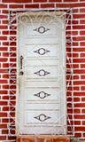 Onlangs geschilderde witte deur achter rooster op verse bakstenen muur stock foto's