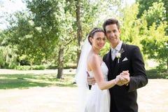 Onlangs het houden van wed van paar die in tuin dansen stock afbeeldingen