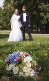 Onlangs wed holdingshanden, huwelijksboeket in de voorgrond Royalty-vrije Stock Afbeeldingen