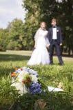 Onlangs wed holdingshanden, huwelijksboeket in de voorgrond Stock Afbeelding