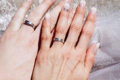 Onlangs wed paar` s handen met trouwringen stock afbeeldingen