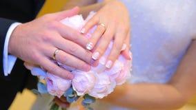 Onlangs wed paar` s handen met trouwringen Bruid en bruidegom met trouwringen op bloemen of huwelijksboeket Onlangs Wed royalty-vrije stock afbeeldingen