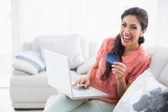 笑的浅黑肤色的男人坐她的沙发使用膝上型计算机购物onlin 免版税库存照片