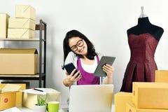 Online-affär, ungt asiatiskt kvinnaarbete hemma för denaffär komrets, små och medelstora företagägare som kontrollerar och packar royaltyfri foto