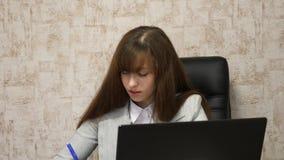 online-aff?rskonversation p? datoren Flicka som i regeringsst?llning sitter i stol p? dator- och tagandeanm?rkningar i anteckning lager videofilmer