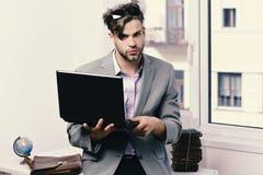 Online arbeiten und Gerätkonzept Kühler Kerl sitzt auf Tabelle und arbeitet Mann oder Manager mit Borste und ernstem Gesicht here Lizenzfreies Stockbild