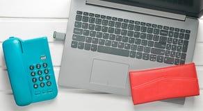 Online-arbete som frilansar begrepp Kontorstelefon, bärbar dator, pråligt drev, plånbok på en vit trätabell Top beskådar Royaltyfri Foto