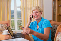 Online banking. A happy senior woman doing online banking with credit card and phone and laptop on the desk Royalty Free Stock Images