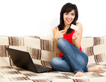 Online Banking. Young Brunette Woman Holding a Card Shopping / Paying / Banking Online royalty free stock photos