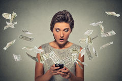 Online banking concept. Shocked woman using smartphone dollar bills flying away Stock Photography