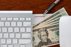 Online Banking. Keyboard and mouse frame deposit slip and twenty dollar bills. pen points to deposit slip all are on top of a brown grain wood royalty free stock image