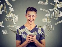 Online banking money transfer, e-commerce concept. Man using smartphone with dollar bills flying away from screen. Online banking money transfer, e-commerce Royalty Free Stock Image