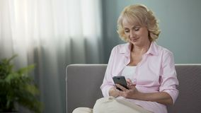 Online banking, senior woman sitting on sofa, using financial app on smartphone. Stock footage stock video