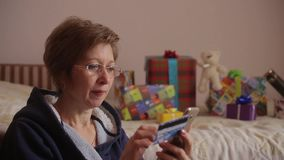 Woman with gifts on the background using smartphone to shopping online with credit card. Online banking. Woman in glasses using smartphone to shopping online stock video