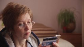 Woman with gifts on the background using smartphone to shopping online with credit card. Online banking. Woman in glasses using smartphone to shopping online stock video footage