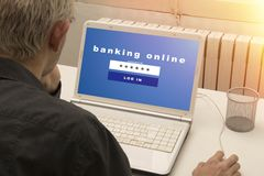"""Online banking. Young man sitting at his desk with a white laptop computer open showing blue screen headed """"banking online"""" and below space for user name and Stock Photos"""