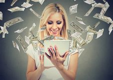 Online-Bankings-Geldüberweisungskonzept Glückliche Frau, die Tablet-Computer mit den Dollarscheinen fliegen weg von Schirm verwen Stockfoto