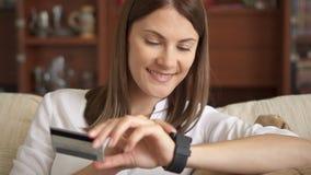 Online-bankrörelsen för härlig kvinna genom att använda smartwatch som direktanslutet shoppar med hemmastadd livsstil för kreditk stock video