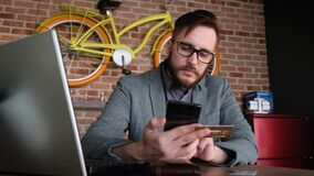 Online-bankrörelsen med den smarta telefonen En trendig modern ung man med ett skägg använder en bankkreditkort för betalning i lager videofilmer