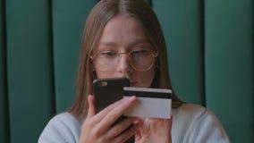 Online-bankr?relsen f?r h?rlig kvinna genom att anv?nda smartphonen som direktanslutet shoppar med hemmastadd livsstil f?r kredit lager videofilmer
