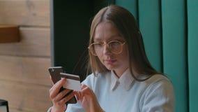 Online-bankr?relsen f?r h?rlig kvinna genom att anv?nda smartphonen som direktanslutet shoppar med hemmastadd livsstil f?r kredit arkivfilmer