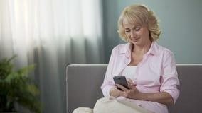 Online bankwezen, hogere vrouwenzitting op bank, die financiële app op smartphone gebruiken stock video