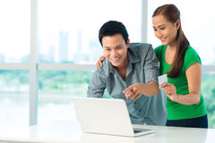 Online bargain. Cheerful Asian couple making an online bargain Stock Photos