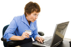 Online Bargain Shopper. Mature woman finds a bargain shopping online.  Isolated on white Royalty Free Stock Photography