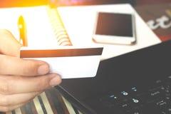 Online betaling, man& x27; s handen die een creditcard over laptop houden Royalty-vrije Stock Fotografie