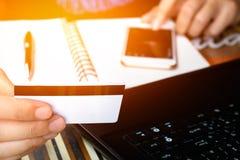 Online betaling, man& x27; s handen die een creditcard over laptop houden Royalty-vrije Stock Foto's