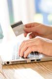 Online-betalning genom att använda bärbara datorn och kreditkorten Fotografering för Bildbyråer