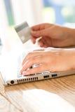 Online-betalning genom att använda bärbara datorn och kreditkorten Arkivbild