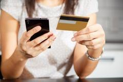 Online-betalning, händer för kvinna` som s rymmer en kreditkort och använder den smarta telefonen för online-shopping Arkivfoto