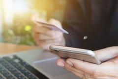 Online-betalning, händer för man` som s rymmer smartphonen och använder kreditering c Royaltyfri Fotografi