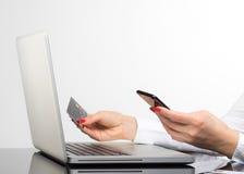 Online-betalning, kvinna` s räcker att rymma en kreditkort och att använda sma Arkivbild