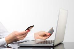 Online-betalning, kvinna` s räcker att rymma en kreditkort och att använda sma Arkivfoto