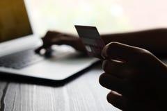 Online-betalning, Man's räcker att rymma kreditkorten och att använda labtop för online-shopping Arkivfoton
